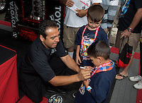 Jul. 27, 2013; Sonoma, CA, USA: NHRA funny car driver Tony Pedregon signing the T-shirt of a young fan during qualifying for the Sonoma Nationals at Sonoma Raceway. Mandatory Credit: Mark J. Rebilas-
