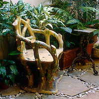 A rustic armchair is placed amongst the ferns on the paved patio