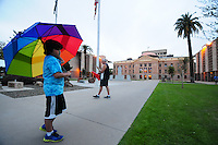 Phoenix, Arizona (February 25, 2014) - A boy holds an umbrella with rainbow colors on the lawn in front of the State Capitol as demonstrators protest against the SB 1062 bill that was sent to the governor's desk for her approval. Arizona's Senate Bill 1062 is galvanizing the LGBT community and other civil and religious groups in the state. A crowd rallied in front of Arizona's Capitol in Phoenix to continue pressuring governor Jam Brewer to veto what they call a discriminatory bill. If approved, SB1062 would amend the existing Religious Freedom Restoration Act, which will allow business owners to deny service to gay and lesbian customers so long as proprietors were acting solely on their religious beliefs. As of this protest, the SB1062 is on Brewer's desk awaiting her approval or veto. Photo by Eduardo Barraza © 2014
