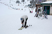 A woman puts on skis at the bottom of Showdown Ski Area on King's Hill in the Little Belt Mountains near Neihart, Montana, USA.