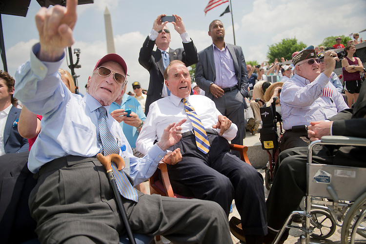 UNITED STATES - MAY 8: Former Sens. John Warner, R-Va., left, and Bob Dole, R-Kan., watch World War II era aircraft fly over the World War II Memorial on the Mall to commemorate the 70th anniversary of the victory in Europe, known as VE Day, May 8, 2015. Warner served in the Navy and Marines and Dole was wounded in WWII while serving in the Army. (Photo By Tom Williams/CQ Roll Call)