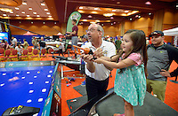 NWA Democrat-Gazette/BEN GOFF -- 04/26/15 Ron Schneider shows Paisley Jones, 2, of Fayetteville how to cast at the Quaker State Casting Pond as her father Trent Jones looks on during the FLW Expo at the John Q. Hammons Center in Rogers on Sunday Apr. 26, 2015.