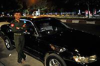 An officer stands next to a black sedan car Mandalay, Burma November 08.<br /> <br /> Photo by Richard Jones