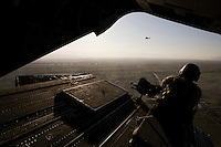 A gunner sits in the back of a helicopter flying over Kunar.