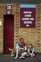 A FAmily of West Ham United supporters seat next to the Boleyn ground turnstiles   before  the Barclays Premier League match between West Ham United and Swansea City  played at Boleyn Ground , London on 7th May 2016