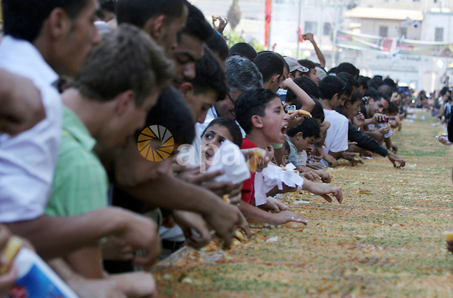 """Palestinians eat of the biggest dish of traditional sweets """"Konafa"""" into the Guinness Book of Records in the West Bank city of Nablus on July 18 2009. Photo by Nedal Shtieh"""