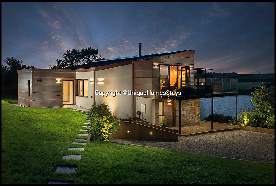 """BNPS.co.uk (01202 558833)Pic: UniqueHomesStays/BNPS<br /> A drab former water bailiff's home has undergone a stunning transformation into a luxury secluded hideaway.<br />  <br /> Architects Mark Camillin and Liam Denny bought the waterside home near Penzance in Cornwall which overlooks a reservoir in an Area of Outstanding Natural Beauty in March 2016. <br />  <br /> The three-storey home is the only dwelling which overlooks the Drift Reservoir and the pair have given it an eye-catching new lease of life.<br />  <br /> The property was originally built in 1961 alongside the Drift Dam and was developed by South West Water as a living quarters for the manager of the dam and the reservoir.<br />  <br /> The dam was constructed in the 1960s to flood the Drift valley and form a reservoir to supply water to west Cornwall.<br />  <br /> However, when the dam was automated the house was sold off a private dwelling and had fallen into disrepair before the intervention of its two owners. <br />  <br /> They have named the home Nevada because of its similarities to an American lake house.<br />  <br /> The upper level of Nevada is clad in copper while the rest of the home is made out of Cornish granite stone.<br />  <br /> There are three bedrooms each with sun decks and a secret garden gate which opens out onto the waterside pathway. <br />  <br /> The inside of the eco-friendly home has been lined with plywood and there is a concrete tile floor.<br />  <br /> A spokesperson for Unique Home Stays said: """"The upper levels of the house have been clad externally with copper, while the lower levels remain as built with Cornish granite stone. <br />  <br /> """"The exterior of the house is uncompromisingly modern - modernism from the 1960s with a feel of a Californian lake side cabin.<br />  <br /> """"The secret garden gate opens out onto the waterside pathway where couples can enjoy romantic moonlit walks. <br />  <br /> """"Fisherfolk can hire a boat and enjoy the clear waters of the Dr"""