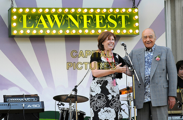 "CHRISTINE WELLS (School Principal) & MOHAMED AL FAYED.At ""Lawnfest"", an open air concert, West Heath School, Sevenoaks, Kent, England..June 25th, 2009.half 3/4 length mohammed grey gray suit black dress white floral print microphone stage  .CAP/FIN.©Steve Finn/Capital Pictures."