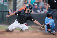 Kannapolis Intimidators catcher Seby Zavala (21) puts the tag on Jose Almonte (16) of the Hickory Crawdads as he slides into home plate at Kannapolis Intimidators Stadium on June 11, 2016 in Kannapolis, North Carolina.  The Crawdads defeated the Intimidators 7-5.  (Brian Westerholt/Four Seam Images)