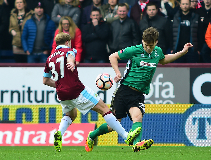 Lincoln City's Sean Raggett vies for possession with Burnley's Scott Arfield<br /> <br /> Photographer Andrew Vaughan/CameraSport<br /> <br /> Emirates FA Cup Fifth Round - Burnley v Lincoln City - Saturday 18th February 2017 - Turf Moor - Burnley <br />  <br /> World Copyright &copy; 2017 CameraSport. All rights reserved. 43 Linden Ave. Countesthorpe. Leicester. England. LE8 5PG - Tel: +44 (0) 116 277 4147 - admin@camerasport.com - www.camerasport.com