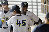 Starting pitcher Tony Dibrell (8) of the Columbia Fireflies is congratulated by Yeizo Campos (45) in the dugout during a game against the Charleston RiverDogs in which he set a Fireflies single-season strikeout record of 138 on Tuesday, August 28, 2018, at Spirit Communications Park in Columbia, South Carolina. Columbia won, 11-2. (Tom Priddy/Four Seam Images)