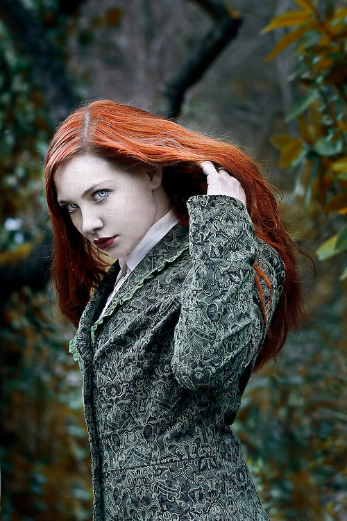 A girl with red hair in the forest.