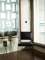 The living room has a strong retro feel, in keeping with the Bauhaus architecture of the building.  In one corner stands a simple metal and wood chair alongside are two metal plant holders. One window is dressed with a plain screen and has plants on the outside sill, the other has a wood venetian blind.