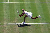 Woman running after a ball on a grass tennis court
