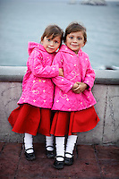 Twins of three sisters in Mazatlan, Mexico, 2009.<br /> I met these three girls with their parents while walking along the coast in Mazatlan. I found it amusing that these young twins in pink emanated such childhood sweetness while their older sister gave a hint of how they might look in their teenage years.