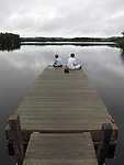 Two boys fishing from a dock on Moxie Pond, East Moxie Township, Somerset County, Maine, USA