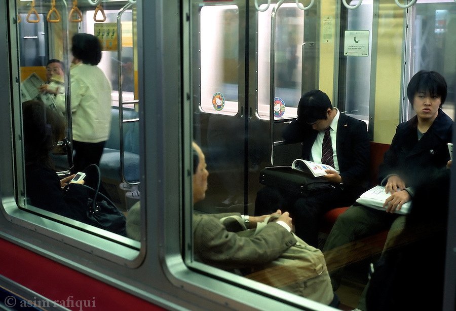 Manga readers on an evening subway train in downtown Tokyo.  It is common to see commuters, both young and old, men and women, passing their commuting horus reading manga magazines and comics on the trains.