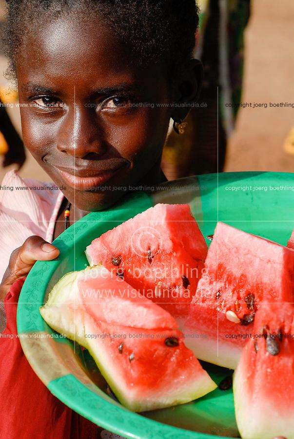 MALI, village Faragouaran , girl sells watermelon pieces on the market / Markt im Dorf Faragouaran, Maedchen verkauft Wassermelone um Geld zu verdienen