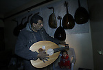 """Hammad Atwa, a Palestinian man who makes lutes, known in Arabic as an """"Oud"""" shows one of his handmade musical instruments at the Khan Younis refugee camp in the southern Gaza Strip on February 19, 2014. Hammad sells his ouds for 300 American dollars a piece. Photo by Eyad Al Baba"""