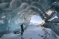 Person standing inside a glacier ice cave along a glacier that flows out of the Alaska Range mountains.