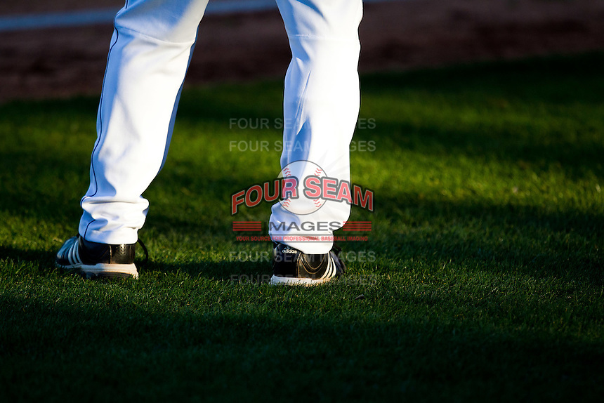 A coach stands on the third base line during a game between the Missouri State Bears and Southern Illinois University- Edwardsville Cougars at Hammons Field on March 9, 2012 in Springfield, Missouri. (David Welker / Four Seam Images)