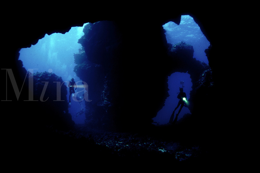 These divers (MR) are entering a dive site of the island of Lanai named Second Cathedral (yes, there is a first as well). Although it appears to be a cavern it more closely resembles a large lava bubble that cracked rather than burst. Lanai, Hawaii.