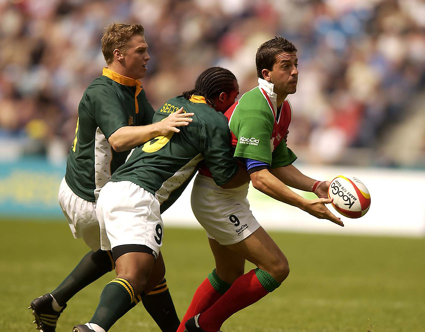 Photo. Jed Wee.Rugby 7s, South Africa v Wales, City of Manchester Stadium, Manchester. 3-8-2002..Wales' Gareth Swales releases the ball under pressure from South Africa's Egon Seconds.