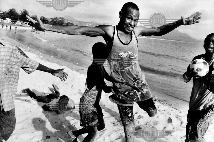 An amputee man playing football on the beach. Amputation was used as a weapon against civilians by RUF rebels during the civil war.