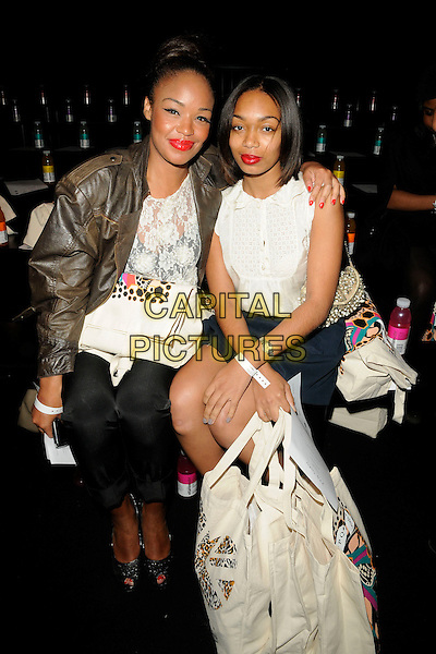 SARAH JANE CRAWFORD & ZARAAH ABRAHAMS .At the PPQ Fashion show during Day 1 of London Fashion Week, BFC Catwalk Show Space, Somerset House, London, England, UK, September 17th 2010..LFW full length sitting down grey gray brown jacket leather white lace top arm around sitting down black trousers bag blue skirt .CAP/CAN.©Can Nguyen/Capital Pictures