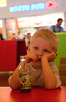 Thoughtful boy eating in a fast food restaurant at Manufaktura entertainment center. Balucki District Lodz Central Poland