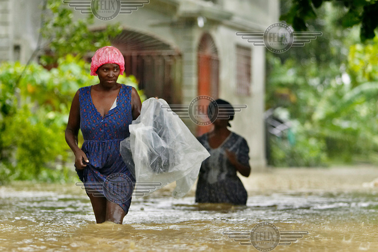 Women walk through flood waters during Hurricane Gustav.