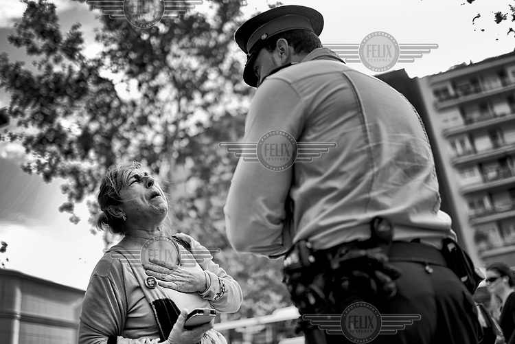 A distressed woman talks to a police officer at the entrance of a branch of the Catalunya Caixa Bank office, during a protest against the bank. Members of PAH (Mortgage Victims Platform) have occupied and closed the bank because they say: 'Catalunya Caixa is one of the worst banks in Spain in terms of eviction levels. In the first six months of 2012 there were 18,424 evictions in Spain.