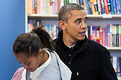"""United States President Barack Obama, right, and daughter Malia, left, shop at One More Page Books in Arlington, Virginia on Small Business Saturday, November 24, 2012. .Credit: Kristoffer Tripplaar  / Pool via CNP..Pool Report 1: Motorcade left the South Lawn [of the White House] at 1:02 p.m. and arrived in Arlington, Virginia, at One More Page Books at 1:15 p.m. for an OTR (Off the Record) Small Business Saturday event with Sasha and Malia.  From the door of the small book shop, which the White House described as an """"independent, neighborhood bookstore,"""" POTUS (President of the United States) could be seen holding up his BlackBerry, apparently looking up a title, as he spoke with shop owner Eileen McGervey. """"Preparation,"""" the president said. """"That's how I shop.""""  Wearing a dark windbreaker against the blustery weather outside, POTUS handed off a stack of about 10 books to the clerk -- pool was too far away to read titles -- (will send in a later report if we get them) and then shook hands with several employees. He then began to wander through the business with his daughters as pool was escorted out.  """"We're doing Christmas shopping,"""" POTUS said to a question from the pool about the fiscal cliff. """"Happy Thanksgiving, folks.""""  POTUS emerged about 10 minutes later to shake hands for a few minutes with two small groups that formed outside the shop on the sidewalk."""
