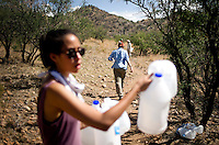 No More Deaths volunteer Hether Vega (cq) holds empty water jugs left by passing migrants on a popular crossing path in Chiminea Canyon outside Arivaca, Arizona from July 21, 2009. The group deposits water and gives medical attention to migrants in need traveling from Mexico through the desert to the United States...PHOTOS/ MATT NAGER