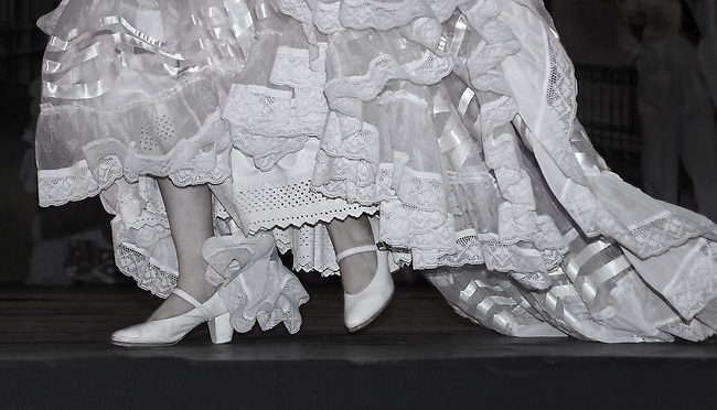 "The lower portion of the white ""wedding"" dress in sheer white enhanced with ruffles, lace and satin ribbon worn by the bride in Boda en La Husteca, one of the traditional dances preformed by the Ballet Folklorico de Mexico in which female dancers wearl costumes designed to swirl with the movement of the dance."
