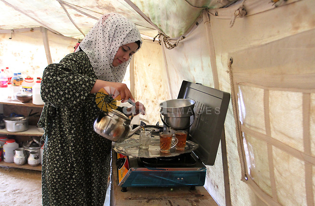 A Palestinian woman prepares tea at a tent near the ruins of her house which witnesses said were destroyed by Israel shelling during a 50-day conflict last summer, east of Khan Younis in the southern Gaza Strip January 27, 2015. The main U.N. aid agency in the Gaza Strip said on Tuesday a lack of international funding had forced it to suspend payments to tens of thousands of Palestinians for repairs to homes damaged in last summer's war. Robert Turner, Gaza director of operations for the United Nations Relief and Works Agency (UNRWA), said in a statement that UNRWA received only $135 million of the $720 million pledged by donors to its cash assistance program for 96,000 refugee families whose homes were damaged or destroyed in the 50-day conflict between the Hamas Islamist movement and Israel. Photo by Abed Rahim Khatib