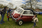 Floral Park, New York, U.S. - April 27, 2014 - Family with young children look at the 1958 BMW Isetta 300 at the 35th Annual Antique Auto Show at Queens Farm. Designed by the Italian refrigerator company ISO, it has a refrigerator-like front door which swings open to let the driver and passenger enter.