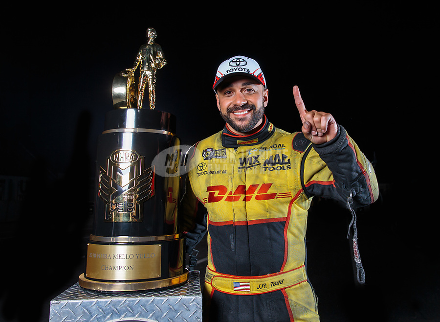 Nov 11, 2018; Pomona, CA, USA; NHRA funny car driver J.R. Todd poses for a portrait as he celebrates with the world championship trophy after winning the Auto Club Finals at Auto Club Raceway. Mandatory Credit: Mark J. Rebilas-USA TODAY Sports