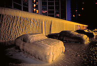 Frozen ice covered cars in parking lot of highrise in Edgewater neighborhood of Chicago, along Lake Michigan east of Sheridan Road, after cold, winter storm. Weather. Chicago Illinois United States Lakefront.