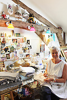 Katie Elliott Armitage, surrounded by the pieces of vintage scrap fabrics that she turns into items to sell or use in her craft worshops