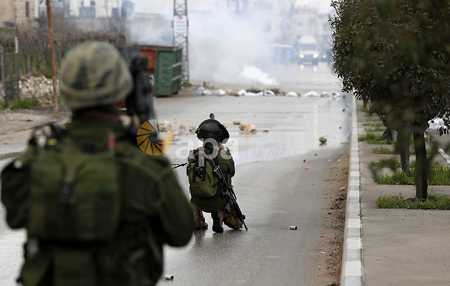 An Israeli soldier fires a teargas canister during clashes with Palestinian protestors following the funeral of Hamza Zamareh in Halhoul, in the West Bank city of Hebron on February 17, 2018. Hamza stabbed a security guard at the entrance of the Israeli settlement Karmei Tzur north of Hebron and was shot dead, the Israeli army said, in the latest violence in the occupied West Bank. Photo by Wisam Hashlamoun