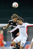 Washington, D.C.- March 29, 2014.Nick DeLeon (14) of D.C. United heads the ball against Daigo Kobayashi (16) of the New England Revolution.  D.C. United defeated the New England Revolution 2-0 during a Major League Soccer Match for the 2014 season at RFK Stadium.
