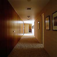 Rooms feed off a main corridor, with one wall clad in wood and the other in fabric and a shag-pile carpet on the floor