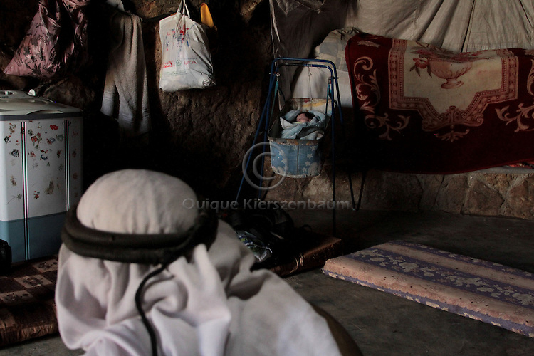 """A baby from the Jabareen family is seen in a cave in Jenba a Palestinian town of 50 families seats in an area called by the IDF as """"Firing Zone 918"""" and is located in the southern Hebron hills near the town of Yatta.  Spread over 30,000 dunams, it includes twelve Palestinian villages.  According to OCHA figures, 1,622 people lived in the area in 2010, and according to local residents the number of inhabitants currently stands at about 1,800. For over a decade, the residents of twelve uniquely traditional Palestinian villages in the area of Masafer-Yatta in the south Hebron hills have lived under the constant threat of demolition, evacuation, and dispossession.The State's insistence on evacuation of Firing Zone 918 in part or in whole, if acceptance by the HCJ, might result in an immediate humanitarian disaster for almost two thousand souls, the destruction of villages, and the eradication of a remarkable way of life that has endured for centuries."""