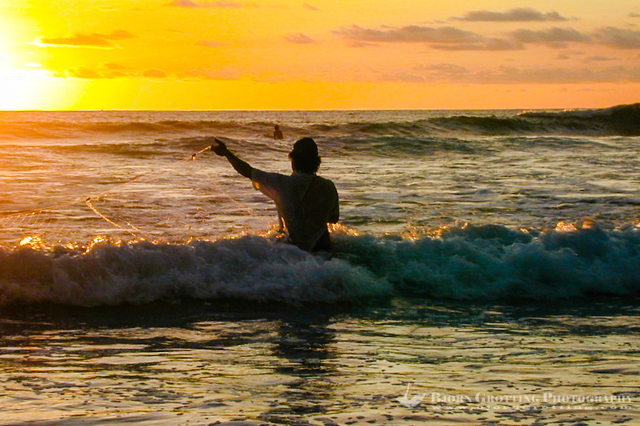 Bali, Badung, Kuta. Kuta Beach just before sunset. A fisherman tries his luck.