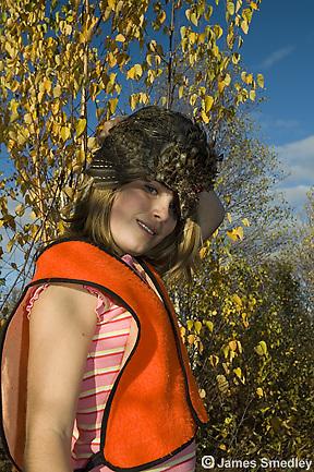Young girl hunter holding shot ruffed grouse