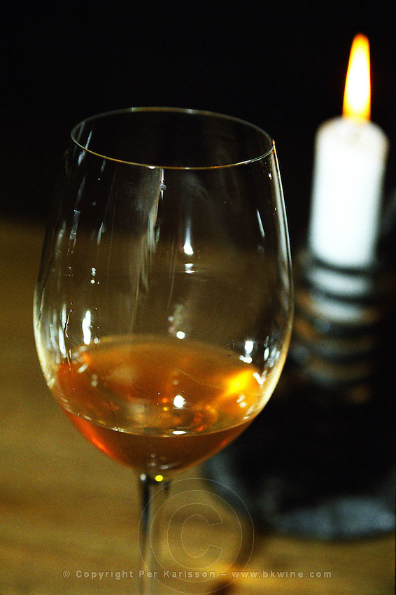 """The Kiralyudvar winery: a glass of Tokaj and a candle in the underground tasting room. The wine is a barrel sample of Eszencia, therefore it is not clear, but extremely concentrated. Kiralyudvar (meaning """"King's Court"""")is run by Istvan Szepsy, considered maybe the best winemaker in Tokaj. he also makes Tokaj under his own name.  Credit Per Karlsson BKWine.com"""