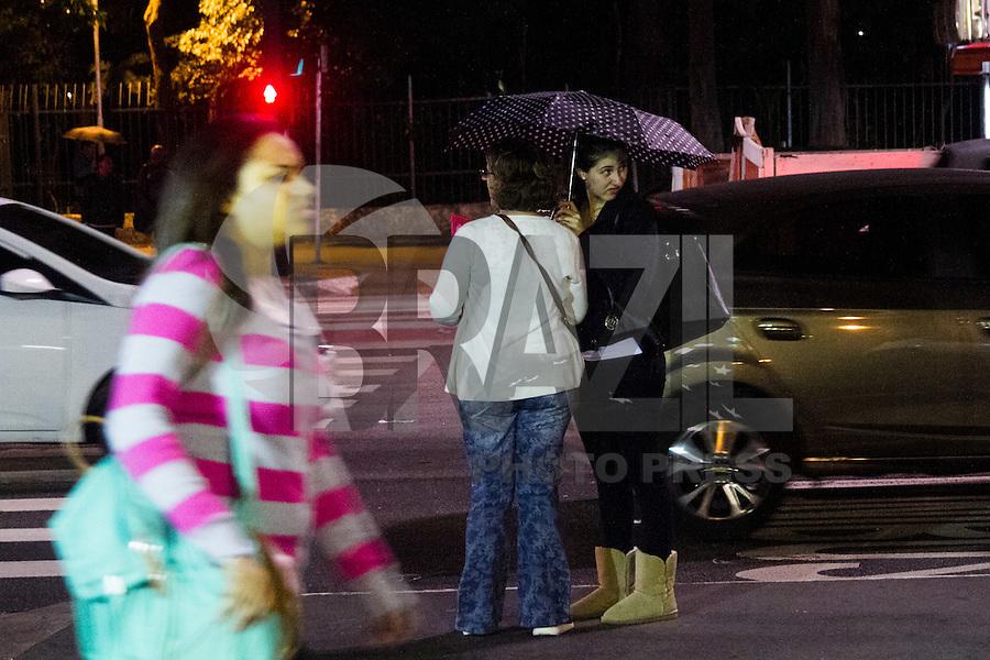 SÃO PAULO, SP, 30.04.2014 - CLIMA TEMPO SÃO PAULO - Pedestre é visto com agasalho e guarda-chuva sob garoa fina  na Avenida Paulista na região centro-sul de São Paulo, na noite dessa quinta-feira ,30. Dados das estações meteorológicas automáticas do CGE aferem a média de 17°C. A máxima prevista para hoje é de 21°C. Durante o dia os percentuais de umidade relativa do ar devem variar entre 50% e 95%. A madrugada terá predomínio de nuvens e chuva fraca. (Foto: Kevin David / Brazil Photo Press).