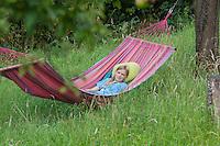 Mädchen, Kind liegt in einer Hängematte, die zwischen Obstbäumen auf einer Wiese aufgespannt ist, wellness, hammock