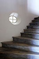 A restored wooden staircase is lit by a single oeil-de-beouf window